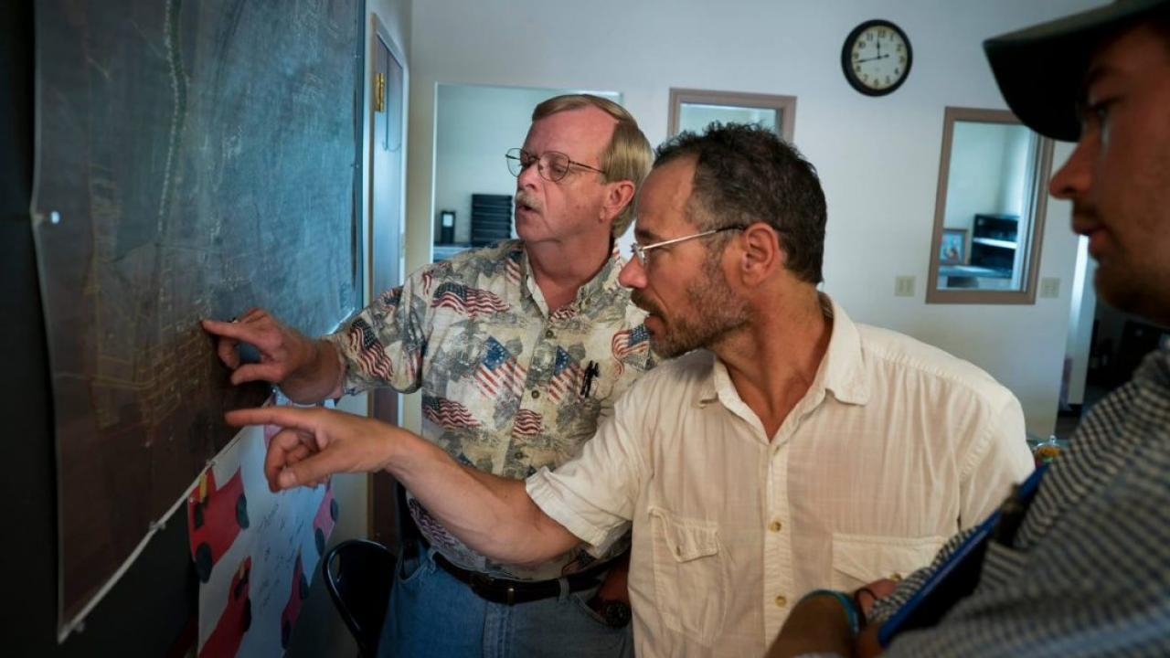 "Dennis Knobloch, Nicholas Pinter and James ""Huck"" Rees look at a map of Valmeyer in the village offices."