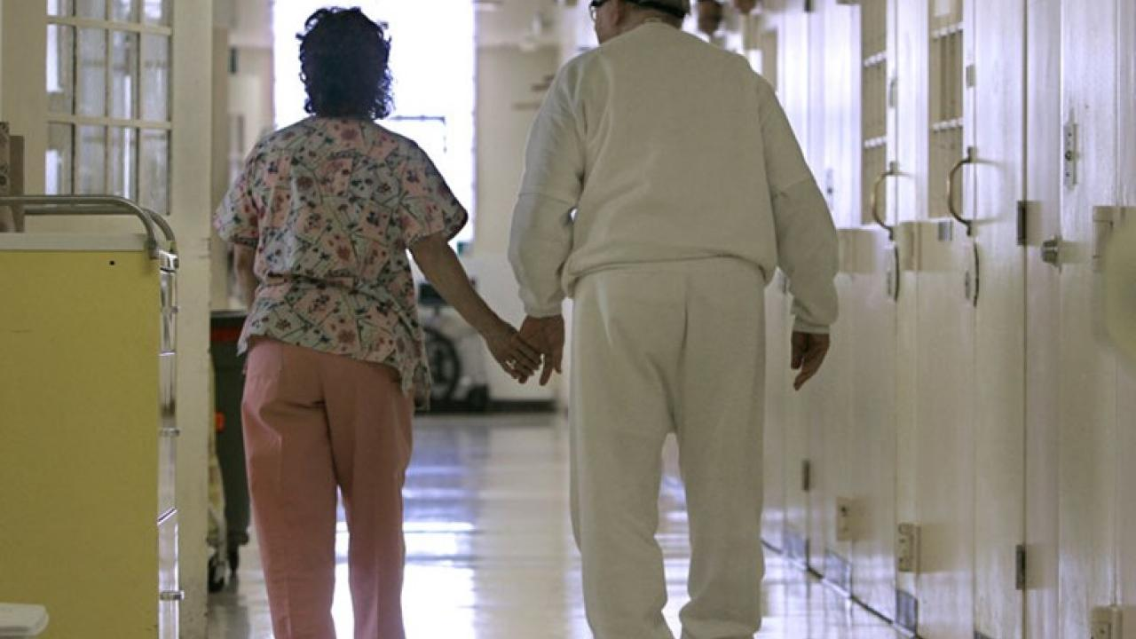 Elderly Latino couple walking down a hospital hallway