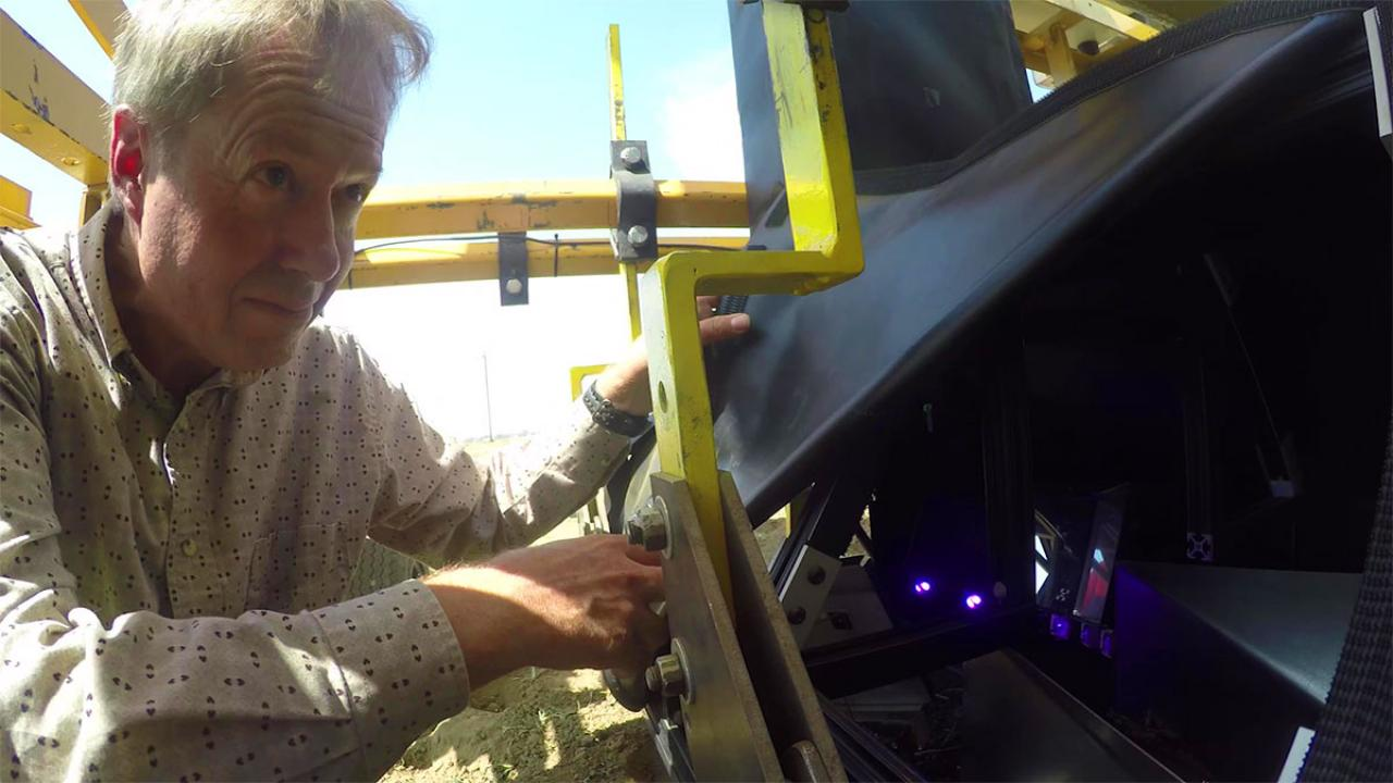 Professor David Slaughter calibrates a smart farm robot