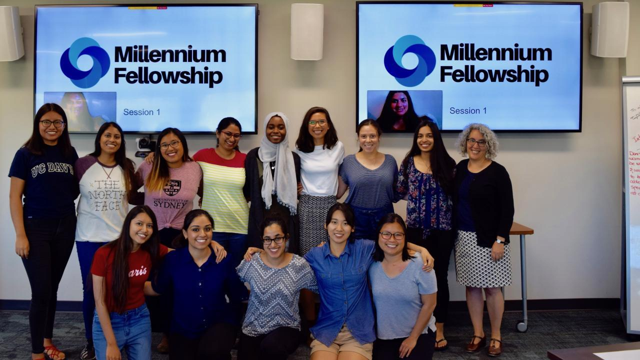 Group of students in front of TV screens that say Millennium Fellowship.