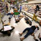 Demonstrators against gun violence lying on the floor of a supermarket in Orlando, Fla., last year.