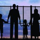 Silhouette of a family at a fence