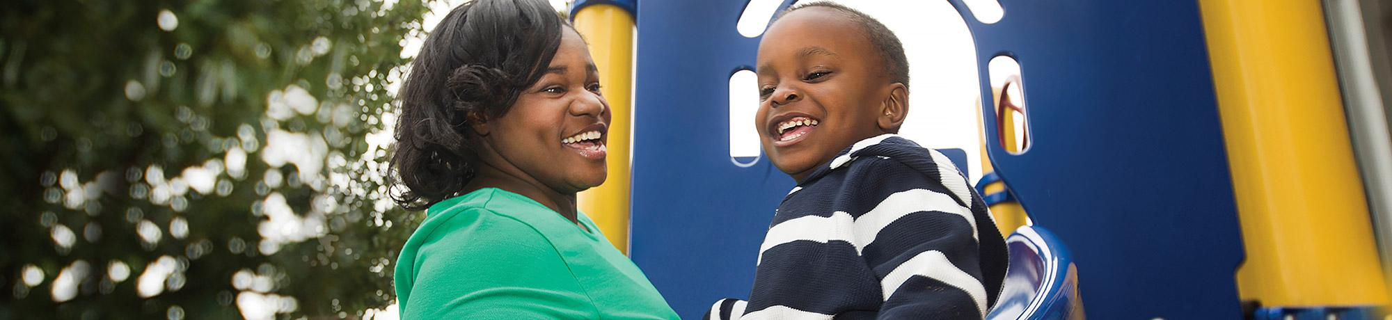 Young mother and son smiling at a playground.